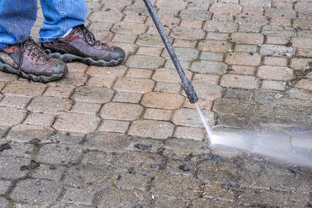 wash: Man Cleaning Patio with a Power Washer Stock Photo