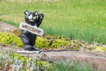 Bear Statue Holding a Welcome Sign Stock fotó