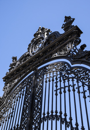 Black Iron Gate Against Blue Sky