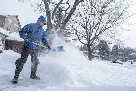 Man Removing Snow with a Shovel in a Suburban Neighborhood