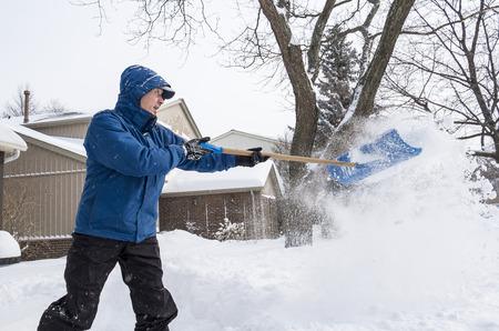 suburban neighborhood: Man Removing Snow with a Shovel in a Suburban Neighborhood