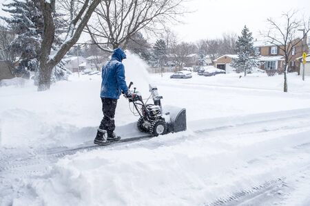 removing: Man Removing Snow with a Snow Blower
