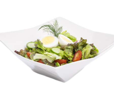 Salad with Hard-boiled Egg on Top Isolated on White