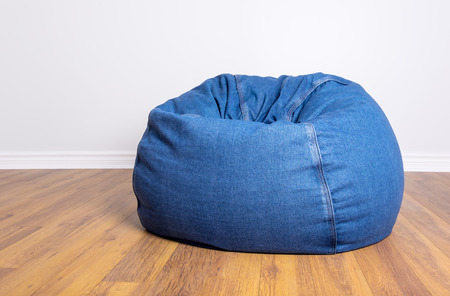 Denim Beanbag Resting on Laminated Flooring Stock Photo