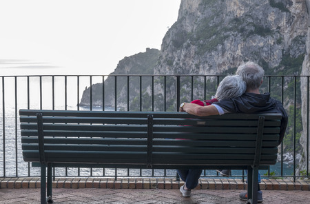snuggling: Elderly Couple Sitting and Snuggling Up Waiting for the Sunset