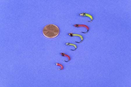 Arrangement of Fishing Flies of Various Sizes on Purple Background Imagens