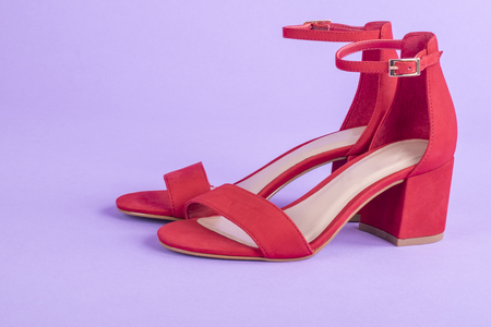 Sandales en daim rouge sur fond violet Banque d'images - 71447559