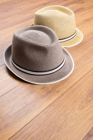 Two Stylish Straw Hats on Laminated Flooring