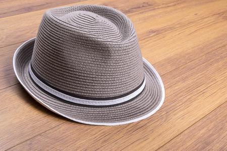 Sombrero de paja de taupe en el suelo laminado Foto de archivo - 71480984