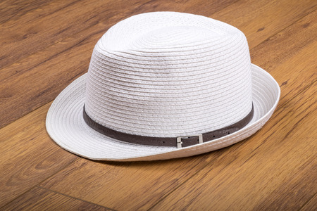 White Straw Hat on Laminated Flooring Stock Photo