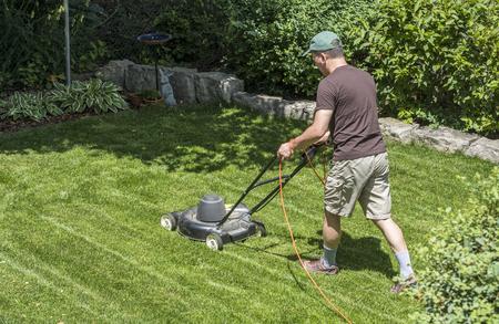 Grass cutting with a lawn mower in a backyard garden Stock Photo
