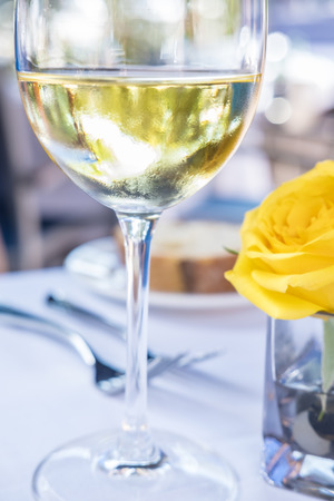 Glass of White Wine and a Yellow Rose on a Restaurant Table