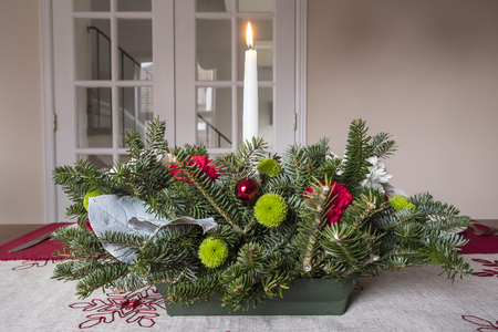 Christmas Table Arrangement or Centerpiece with flowers, evergreen branches and White Lit Candle