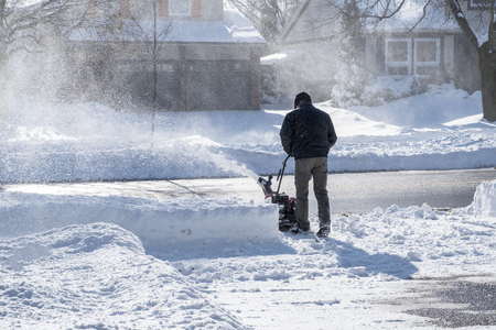 Man Removing Snow with a Snowblower on a Sunny Day 版權商用圖片