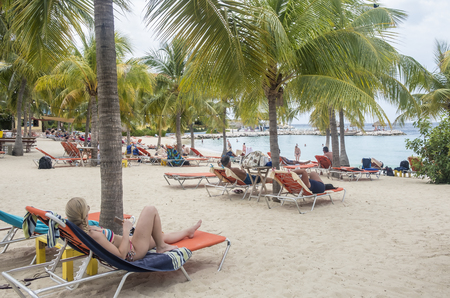 Blue Bay, Curacao - April 11, 2018 - People in their beach chairs sunbathing at Blue Bay Resort Editorial