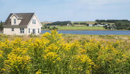 Beautiful Scenic View of a Little House by the Sea with Golden Rod in the Foreground and Farmland in the Background, Victoria By the Sea, Prince Edward Island, Canada Reklamní fotografie