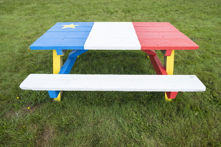 Picnic Table Painted with Colors of the Acadian Flag Foto de archivo