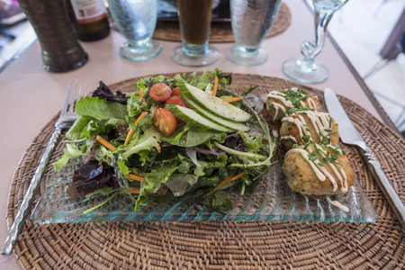 Crab Cakes with Fresh Green Salad Served in a Restaurant in PEI Stock Photo