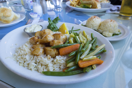 Cooked Scallops Served with Beans and Baby Carrots on a Bed of Rice, with Side of Creamy Potato Salad