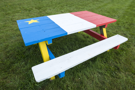 Picnic Table Painted with Colors of the Acadian Flag Stock Photo