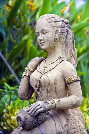 molded woman Thai figure in the flower garden( , the molded figure in public nobody park is owner of ) ,  photo