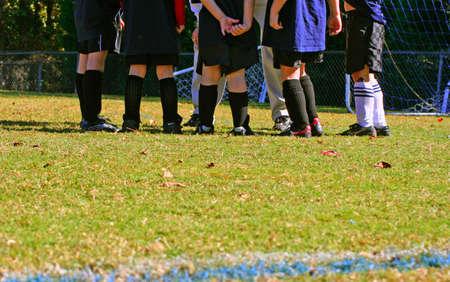 Kids soccer team in coachs huddle