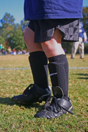 Boys cleats and shinguards just before soccer practice Stock Photo