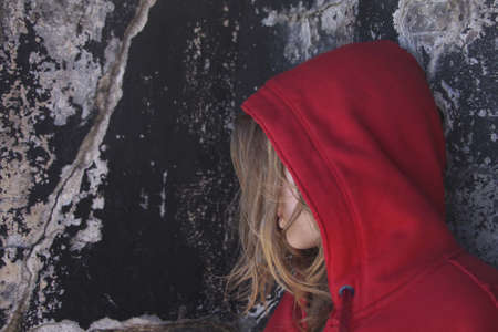 hooded: Girl in red against ancient wall Stock Photo