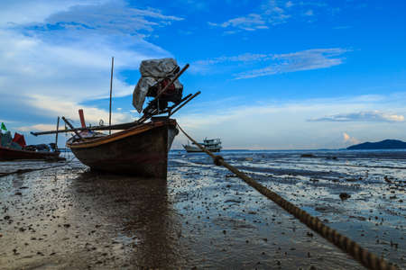 decreased: Longtail boat parked shallow due to sea water decreased. Stock Photo