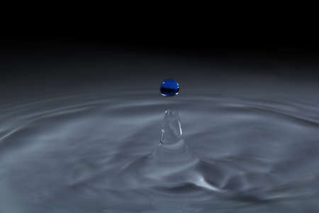 Blue water droplets have a dark background.