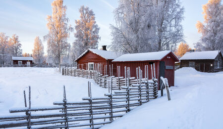 Open-air museum in Gammelstad, Sweden in winter with old small buildings and traditional stack fence