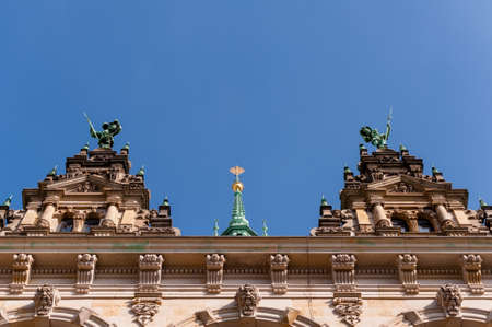 Top of the tower of the Town Hall Hamburg, viewed from the courtyard at daylight and blue sky.