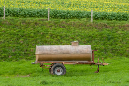 Aged tank wagon on a meadow spending water for cows in summer.