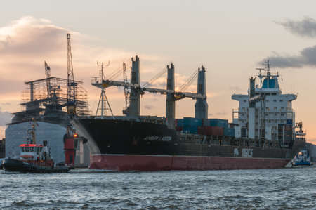 Hamburg, Germany - 01. December 2013: Freighter Amber Lagoon, since 2017 named Magnolia, 4 cranes midship, arrives in Hamburg in the evening. Sajtókép