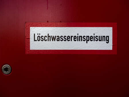 Red lockable cabinet with Hydrant inside for fire fighting in Germany. Loeschwassereinspeisung means extinguishing water supply.