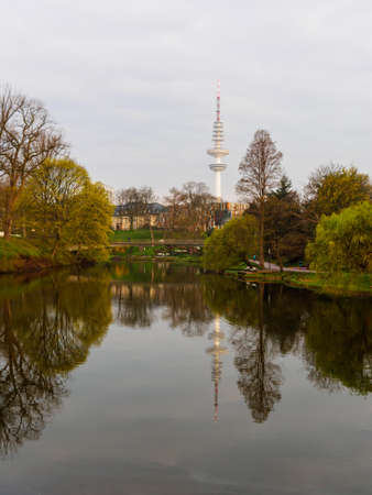 Lake in the park Planten un Blomen an TV tower in background at calm morning in in spring in Hamburg.