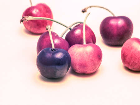 Seven surreal cherries isolated on light background.