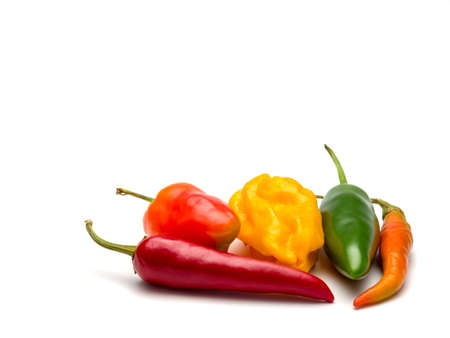 Five peppers of different color and shape isolated on white background. Selective focus. Stock Photo