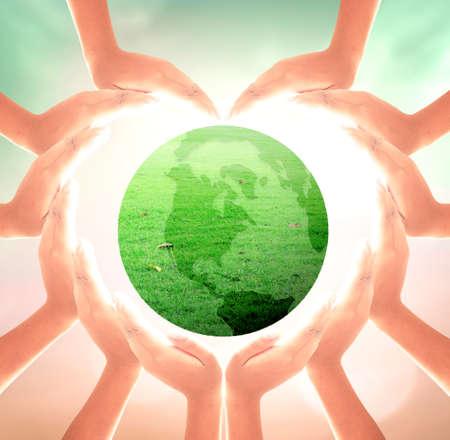世界環境デイコンセプト:ぼやけた自然の背景の上に草の地球儀を保持する手のハートの形 写真素材