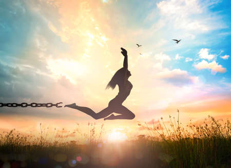 International day for the remembrance of the slave trade and its abolition concept: Silhouette of a girl jumping and broken chains at autumn sunset meadow with her hands raised