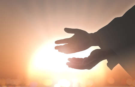 Ascension day concept: Silhouette hands of God over blurred autumn sunset background Banco de Imagens