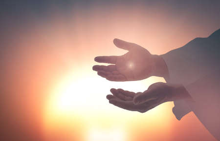 Easter Sunday concept: Silhouette scars in hands of Jesus Christ on sunrise background Archivio Fotografico