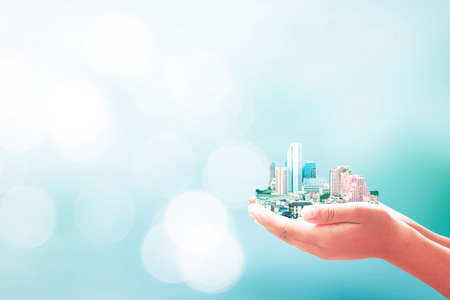 Sustainable development goals (sdgs) concept: Human hands holding hotel in big city on blurred nature background