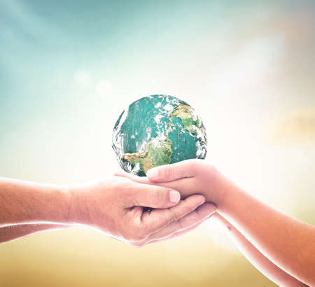International day of peace concept: Children hands holding earth global over blurred abstract nature background.