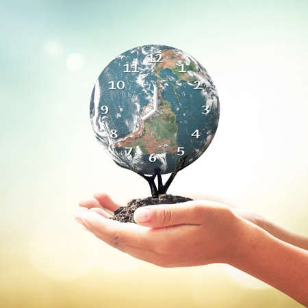 Biological concept: Human hands holding biological clock of earth globe tree on blurred beautiful sunset background.
