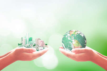 Corporate Social Responsibility (CSR) concept: Businessman and entrepreneurship handing big city and earth globe over blurred blue nature background. 免版税图像