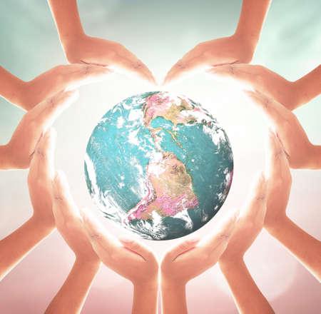 prevent corona virus concept: Heart shape of hands holding earth globe over blurred nature background.