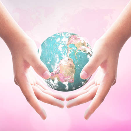 Human hands holding earth global over blurred city night background.