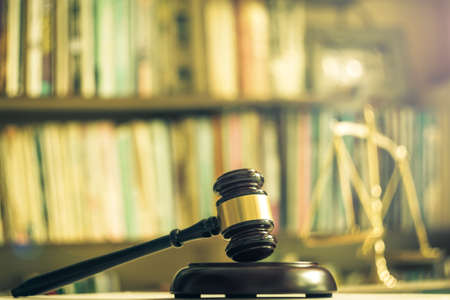 International human rights day concept: Wooden judge gavel with scales on library