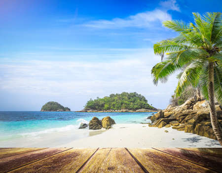 Travel concept: Wooden table front view of coconut palm tree at beach scene background. Seascape in south of Thailand, Asia 免版税图像